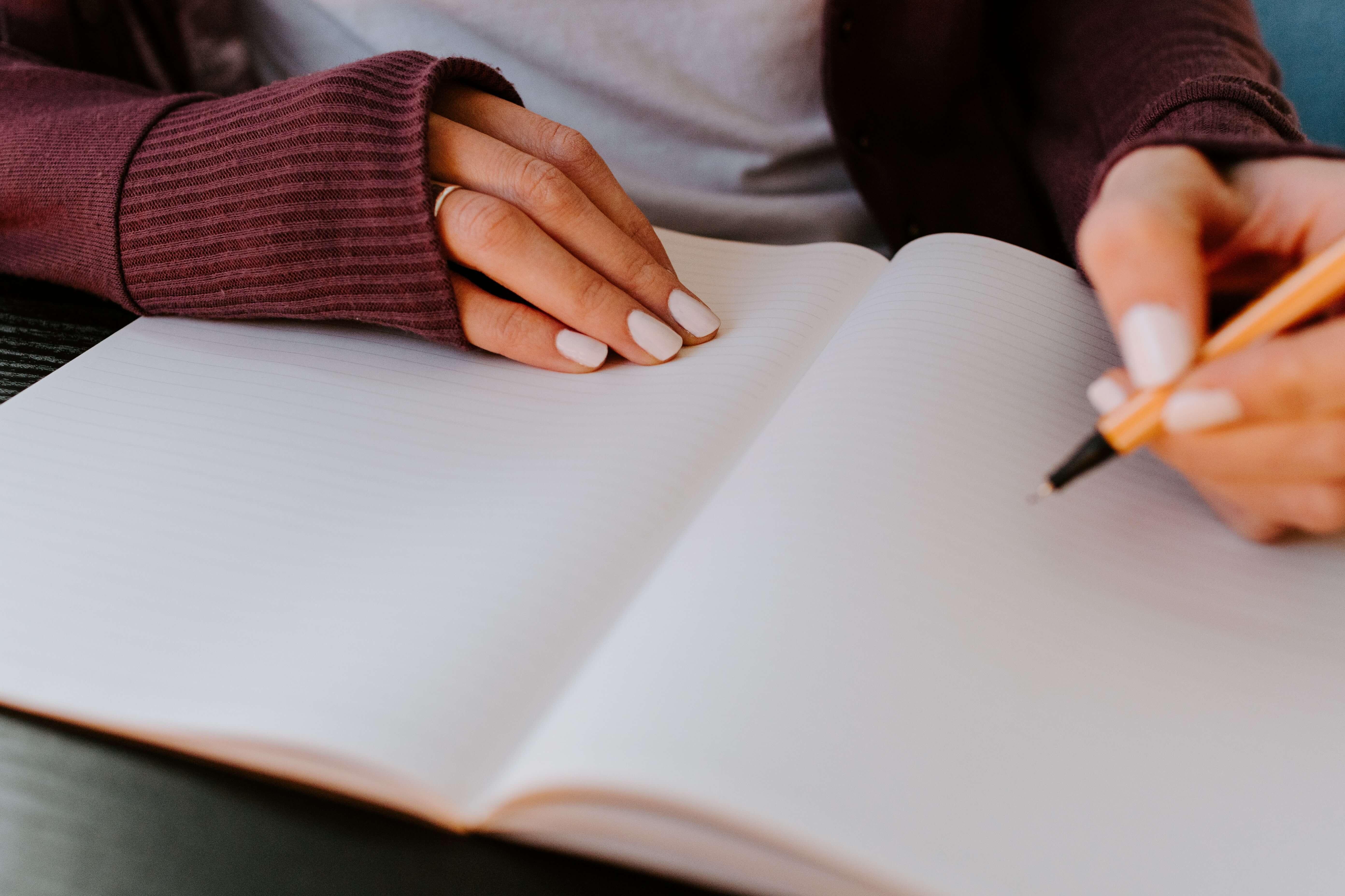 ノートを書く女性の手元